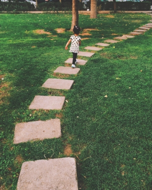 Layla leaving all kind of playground that the park provided and playing with this stone pathway!