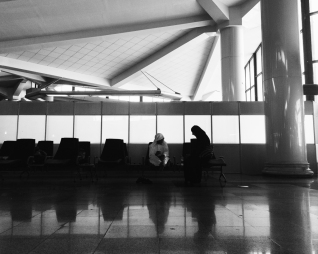Girl is sitting beside her father waiting for the plane to be ready at the terminal in Mashhad Airport