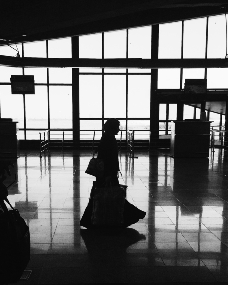 A saudi girl at the terminal in Mashhad Airport taking her bags and heading to the plane door